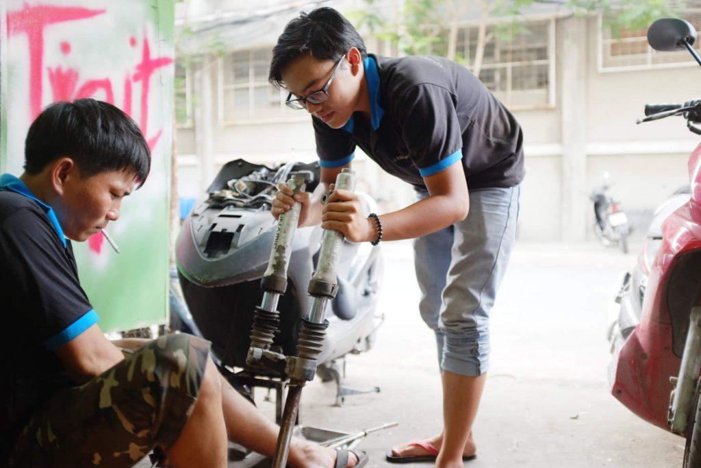 Vietnamese mechanics fixing a motorbike suspension