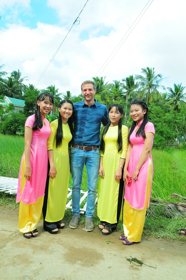 westerner posing with Vietnamese in ao dai