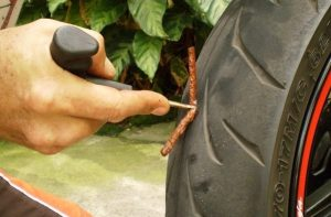 A flat tire on a tubeless tire is fixed with a piece of rubber and some glue